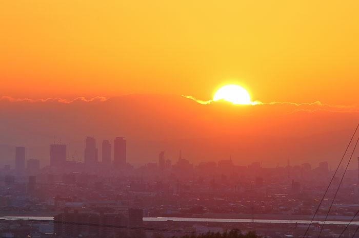名古屋駅周辺の高層ビル群と太陽が半分くらい昇った瞬間