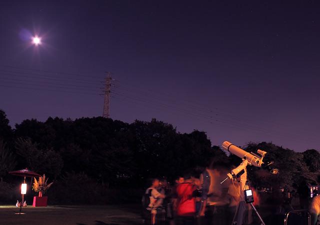 天体望遠鏡で月を観測する人々
