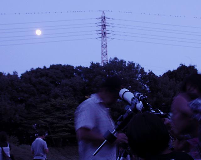 望遠鏡で満月を観賞する少年