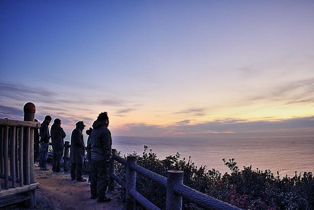 海から昇る初日の出を待つ人物