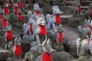 赤い涎掛けをつけた狐の石像がズラリ