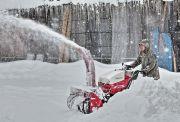 合掌造りの家の前を除雪する人物